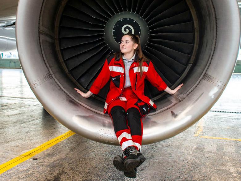 Junge Flugzeugmechanikerin sitzt im Fan des Flugzeugtriebwerks © Scheichel