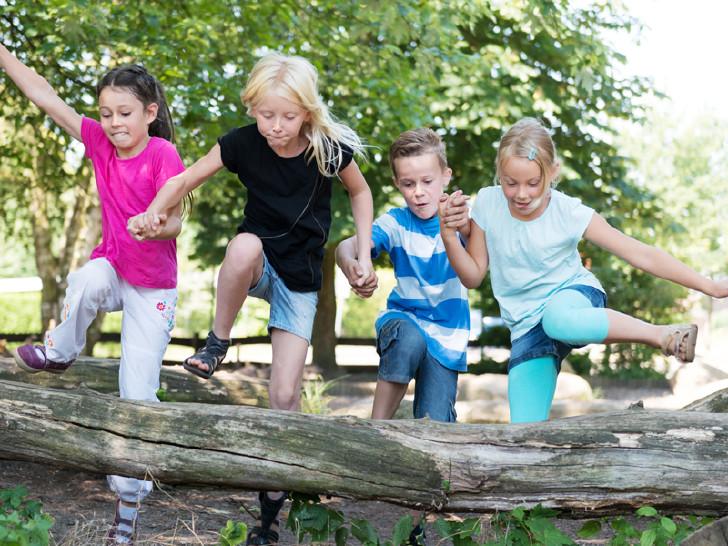 Kinder springen über Baum © Christian Schwier